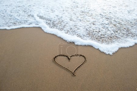 Photo for Heart shape sign erasing by ocean wave on sandy beach - Royalty Free Image