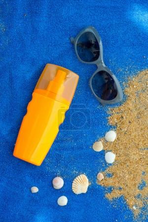 sunscreen bottle on blue towel