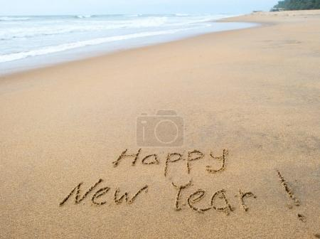 Photo for Happy new year sign on tropical beach sand - Royalty Free Image