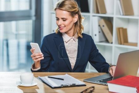 Photo pour Portrait de femme d'affaires souriant à l'aide de smartphone sur lieu de travail avec ordinateur portable et contrat au bureau - image libre de droit