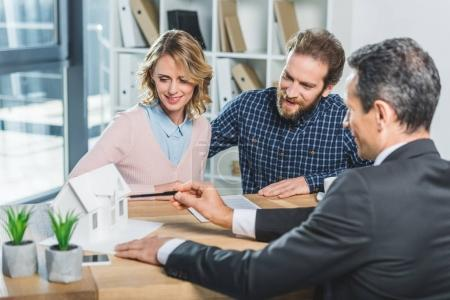 Photo for Portrait of couple having meeting with realtor in real estate agency office - Royalty Free Image