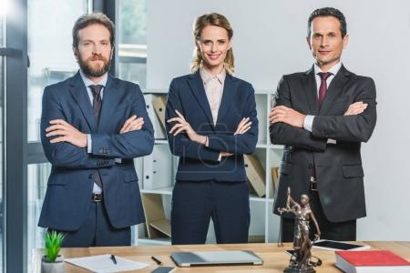 Photo for Portrait of lawyers in suits with arms crossed looking at camera while standing at workplace - Royalty Free Image