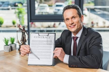 Photo pour Portrait de l'avocat souriant pointant à contrat à la main tout en étant assis au milieu de travail au bureau - image libre de droit