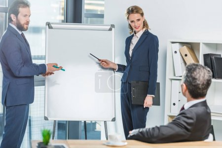 Photo for Lawyers in suits pointing at white board during meeting with colleague in office - Royalty Free Image