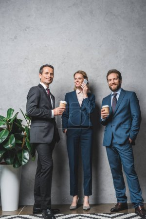 Photo for Smiling business people with coffee to go looking at camera while colleague talking on smartphone - Royalty Free Image