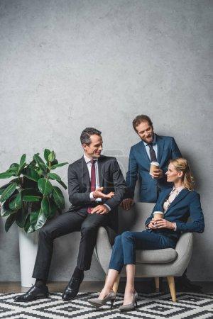 Photo pour Collaborateurs dans des costumes ayant la conversation ensemble au bureau - image libre de droit