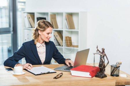 Photo pour Portrait de l'avocat souriant travaillant sur ordinateur portable au lieu de travail avec des documents et la tasse de café au bureau - image libre de droit