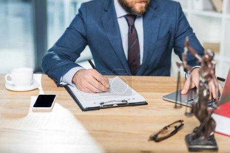 Photo pour Recadrée tir d'avocat, faire de la paperasse et utilisant l'ordinateur portable à l'espace de travail au bureau - image libre de droit