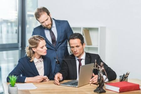Photo pour Portrait de groupe d'avocats ciblées, l'utilisation d'ordinateur portable sur le Bureau - image libre de droit