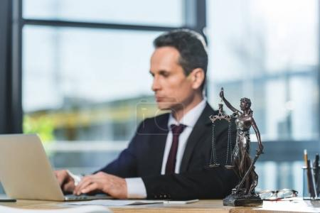 Photo for Selective focus of focused lawyer working on laptop at workplace with femida in office - Royalty Free Image