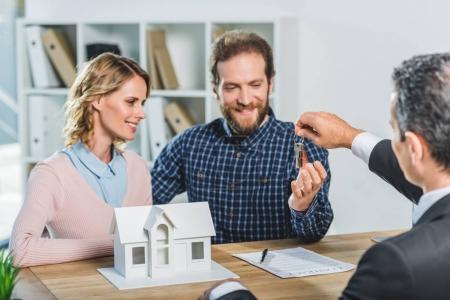 Photo pour Portrait de couple heureux, obtenir des clés de nouveau domicile de l'agent immobilier au bureau - image libre de droit