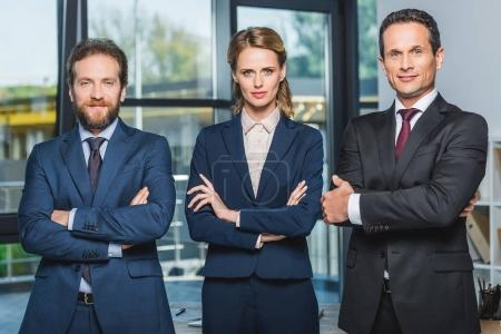 Photo for Portrait of lawyers in suits with arms crossed looking at camera while standing in office - Royalty Free Image