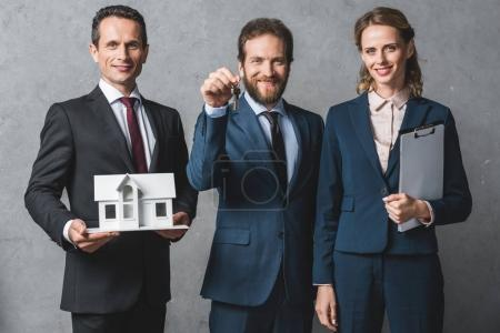 Photo for Portrait of smiling business people with house model, keys and folder looking at camera - Royalty Free Image