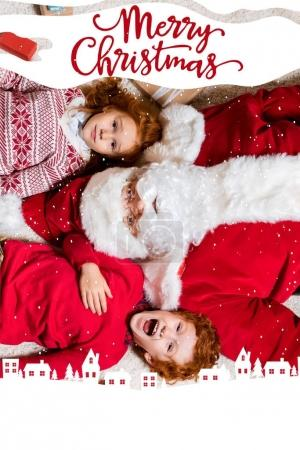Photo for Overhead view of santa claus and little kids lying on floor with gifts together, with winter city illustration and merry christmas lettering - Royalty Free Image