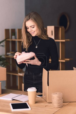 portrait of beautiful entrepreneur packing products for customers in cardboard boxes at home office