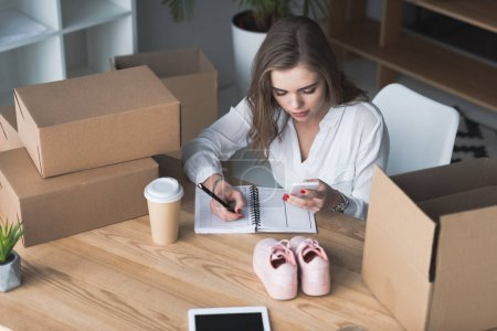high angle view of businesswoman with smartphone in hand making notes