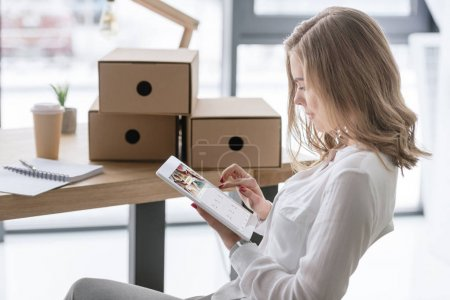 Photo for Side view of young businesswoman using digital tablet - Royalty Free Image