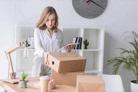 portrait of young businesswoman with cardboard box and tablet in hands