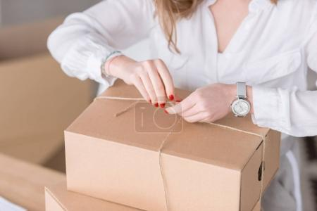Photo for Cropped shot of entrepreneur packing customers purchase in cardboard boxes at home office - Royalty Free Image