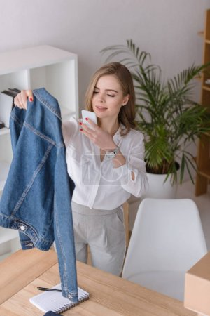 portrait of beautiful businesswoman taking picture of product on smartphone at office
