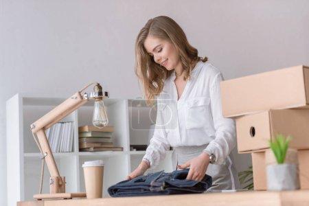Photo pour Jeune entrepreneur souriant emballage clients achat au bureau à domicile - image libre de droit