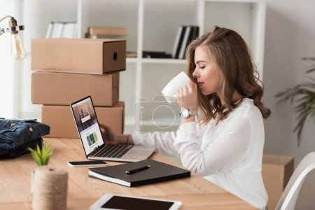 side view of businesswoman drinking coffee while working on laptop at table