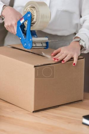 Photo for Partial view of entrepreneur packing customers parcel with adhesive tape - Royalty Free Image