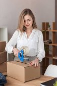 portrait of young entrepreneur packing customers parcel with adhesive tape