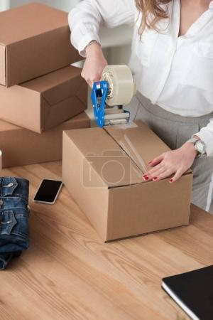 partial view of entrepreneur packing customers parcel with adhesive tape