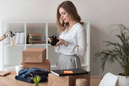 side view of entrepreneur looking at products pictures on photo camera at home office