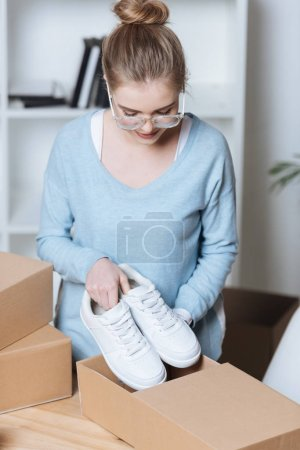 entrepreneur putting shoes into cardboard box while packing customers purchase at home office