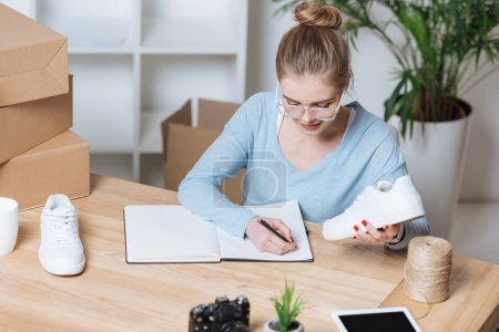 portrait of young entrepreneur with pair of shoes making notes in notebook at home office