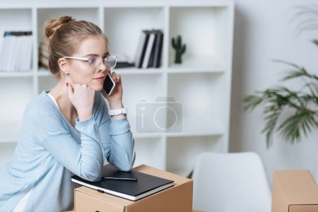 side view of online shop proprietor talking on smartphone during work at home office