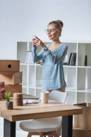 online shop owner taking picture of product on smartphone at home office