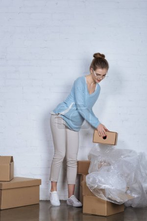 online shop owner with cardboard boxes working at home office