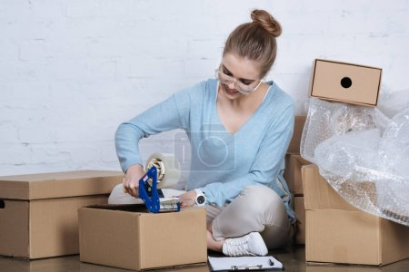 smiling entrepreneur packing parcel with adhesive tape at home office