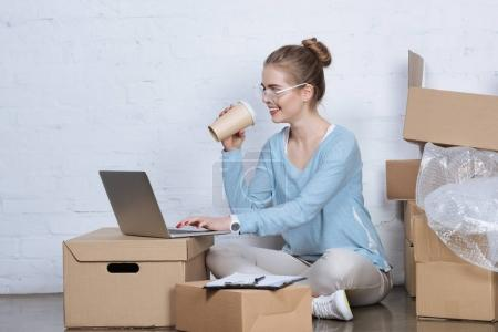 side view of smiling businesswoman with coffee to go typing on laptop at home