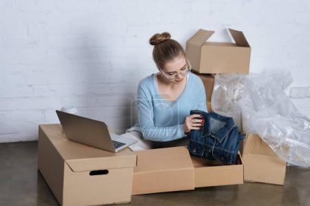 young entrepreneur putting denim jacket into cardboard box while packing products at home office