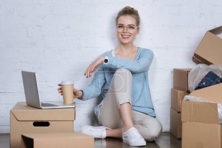 Photo pour Entrepreneur souriant avec café pour aller assis sur le sol au bureau à la maison - image libre de droit