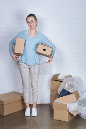 cheerful entrepreneur holding cardboard boxes and looking at camera at home