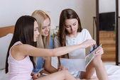 multiethnic girls sitting on bed and reading fashion magazines
