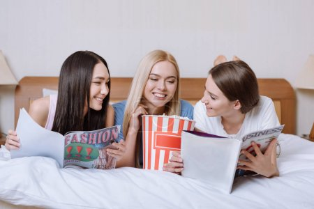 multiethnic friends lying on bed with popcorn and reading magazines