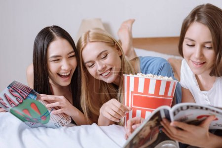 smiling multiethnic girls lying on bed with popcorn and reading magazines