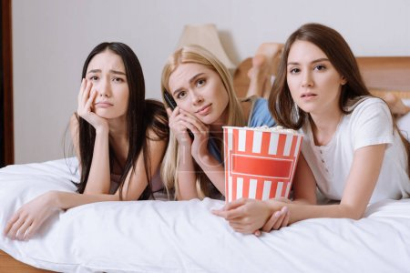 sad multiethnic girls lying on bed with popcorn and watching tv