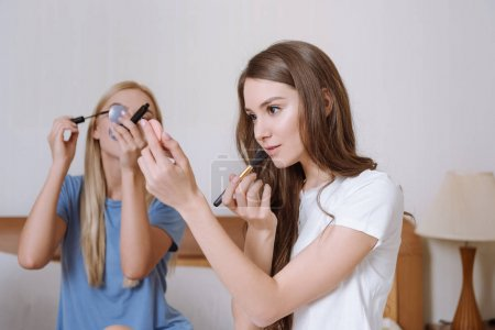 two friends sitting on bed and doing makeup