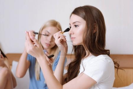 friends sitting on bed and doing makeup