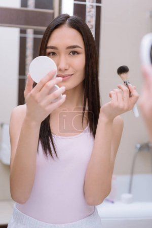 asian girl holding foundation powder and makeup brush in bathroom