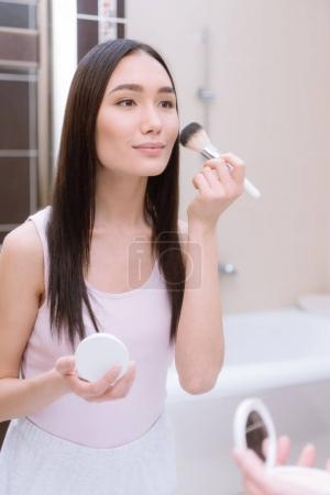 attractive asian girl applying foundation powder with makeup brush in bathroom