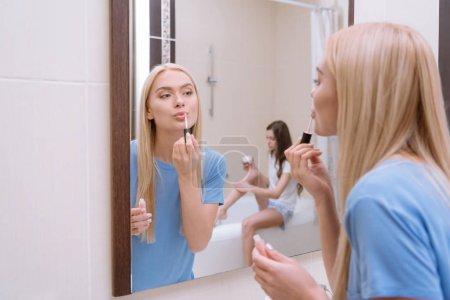 attractive girl applying lips gloss in bathroom
