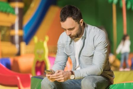 bearded man sitting and using smartphone in entertainment center
